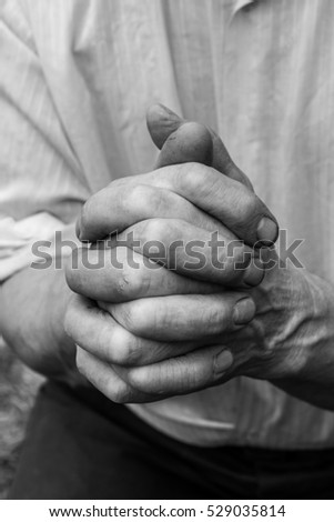 A man holds his hands in front of him. Fingers intertwined.  #529035814
