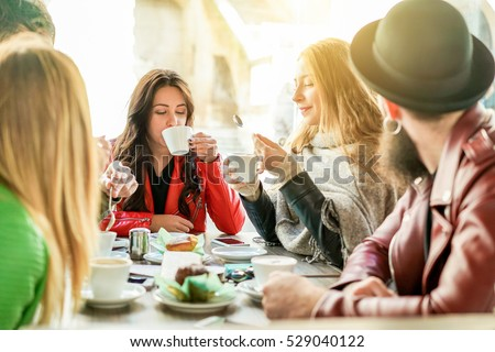 Young friends toasting coffee and doing breakfast in bar bakery shop - Happy hipster people drinking cappuccino and eating muffins - Friendship concept - Focus on center girl - Warm filter