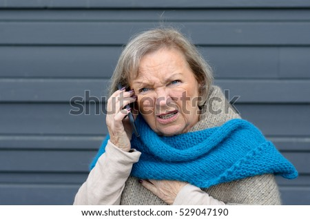 Confused elderly woman chatting on her mobile phone frowning in puzzlement as she listens to the conversation #529047190