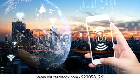 Internet of things , iot , smart home , smart city and network connect concept. Human hand holding white phone and iot icon with city sunset view and earth furnished by NASA. background and wifi icons #529058176