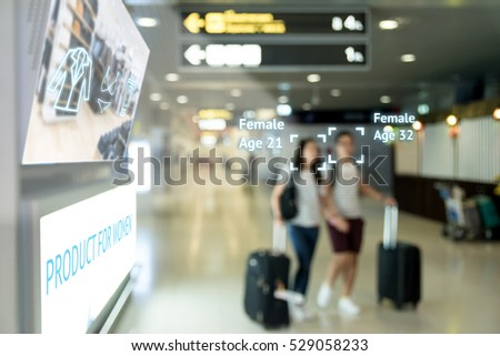 Intelligent Digital Signage marketing and face recognition concept. Two women walk through interactive artificial intelligence digital advertisement in retail shopping Mall.