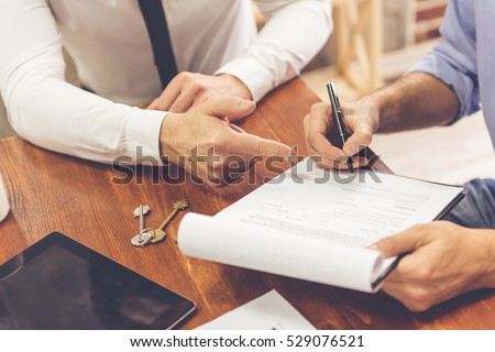 Cropped image of man is signing documents while talking with realtor #529076521