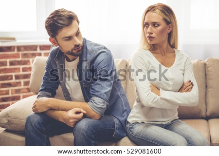 Beautiful couple is sitting back to back on the couch and looking offended at each other while having a quarrel #529081600