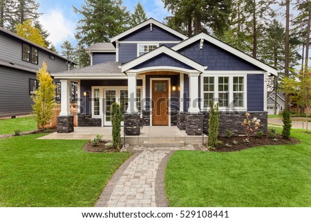 Beautiful exterior of newly built luxury home. Yard with green grass and walkway lead to ornately designed covered porch and front entrance.  #529108441