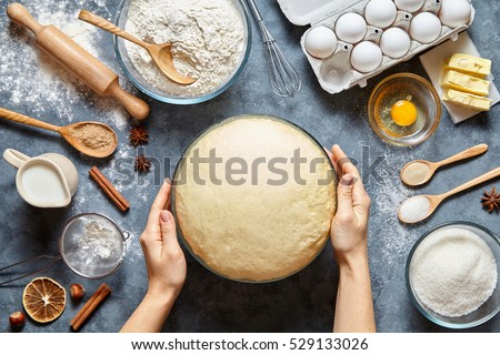 Hands working with dough preparation recipe bread, pizza or pie making ingridients, food flat lay on kitchen table background. Butter, milk, yeast, flour, eggs, sugar pastry or bakery cooking. Royalty-Free Stock Photo #529133026