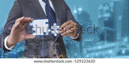 Business solutions, success and strategy concept. Businessman hand connecting jigsaw puzzle with cyan city background. Double exposure. #529223620