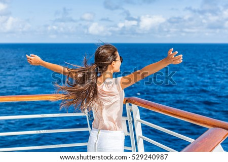 Cruise ship vacation woman enjoying travel vacation at sea. Free carefree happy girl looking at ocean with open arms in freedom pose. Royalty-Free Stock Photo #529240987