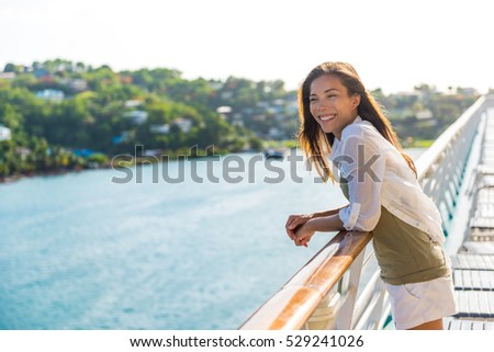 Cruise ship vacation Asian woman relaxing on deck enjoying view from boat of port of call city on St. Lucia island in the Caribbean. Happy casual tourist girl outside on tropical holiday destination. Royalty-Free Stock Photo #529241026