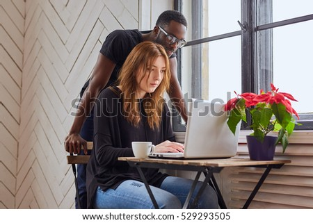 African American male and Caucasian female working with a laptop at the table. #529293505