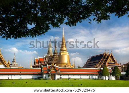 Temple of the Emerald Buddha Wat Phra Kaew with Golden Stupa in Bangkok at sunset #529323475