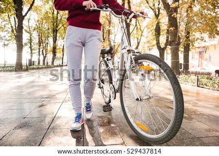 Cropped image of young caucasian woman walking with her bicycle in the street #529437814