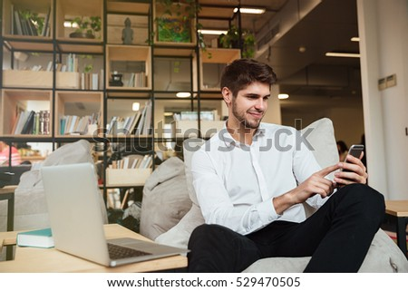 Happy businessman dressed in white shirt sitting in cafe and chatting by phone while using laptop #529470505