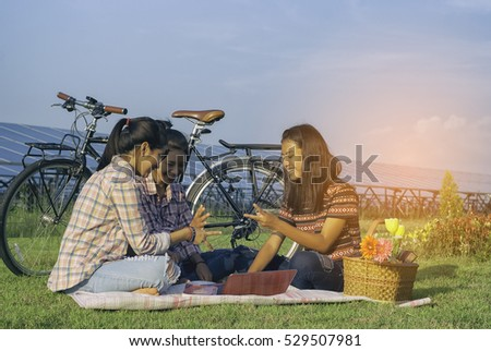 Group of girls enjoying picnic in the solar farm, Three girls on vacation having fun, social networking and teenage.