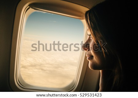 Young woman looking through window in airplane #529531423
