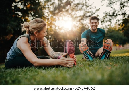 Fitness couple stretching outdoors in park. Young man and woman exercising together in morning. Royalty-Free Stock Photo #529544062