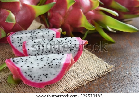 Healthy dragon fruits on sackcloth and brown wooden background