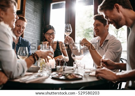 Young man raising his glass of wine with friends at restaurant. Young people enjoying dinner at a cafe. #529580203