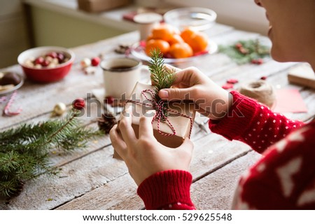 Unrecognizable woman wrapping and decorating Christmas present #529625548