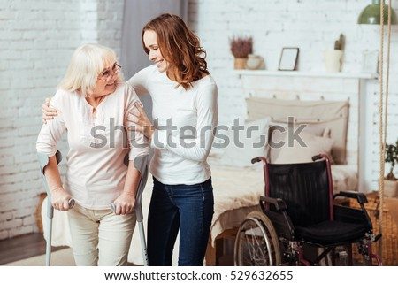Pleasant caring woman helping with rehabilitation her disabled grandmother Royalty-Free Stock Photo #529632655
