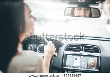 Driver in rear-view mirror. Rear view of attractive young woman in casual wear looking in rear-view mirror and smiling while driving a car  Royalty-Free Stock Photo #529653457