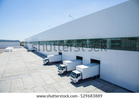 facade of an industrial building and warehouse with freight cars in length Royalty-Free Stock Photo #529683889