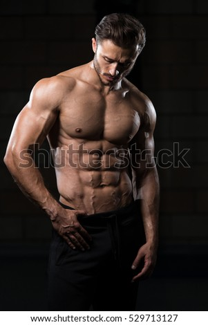 Handsome Man Standing Strong In The Gym And Flexing Muscles - Muscular Athletic Bodybuilder Fitness Model Posing After Exercises #529713127