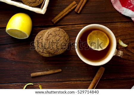 Cookies, cup of tea, cinnamon, lemon are on the table, rustic flat lay photo #529714840