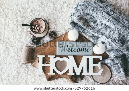 Winter homely scene, scandinavian style. Warm knit sweater, candles, cup of sweet cocoa with marshmallows and other decor on tray in bed. Wooden craft letters Welcome Home. Lazy cold weekend. #529752616