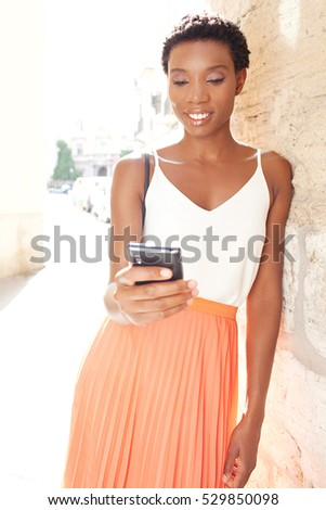 Smiling portrait of professional black tourist woman visiting old classic city with stone walls on holiday, using smart phone, outdoors. African American woman using technology, travel exterior. #529850098