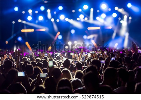 Hand with a smartphone records live music festival, Taking photo of concert stage, live concert, music festival, happy youth, luxury party, landscape exterior. Royalty-Free Stock Photo #529874515