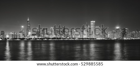 Black and white panoramic picture of Chicago city skyline with reflection in Lake Michigan at night.