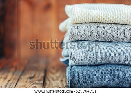 Pile of knitted winter clothes on wooden background, sweaters, space for text. Toning image. #529904911