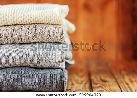 Pile of knitted winter clothes on wooden background, sweaters, space for text #529904920