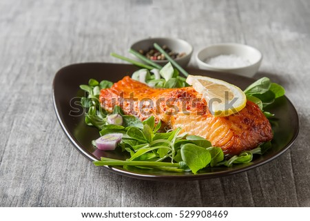 One piece of baked salmon grilled pepper lemon and salt on a brown plate with lettuce leaves. wood background #529908469