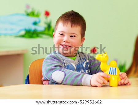 cute kid with down's syndrome playing in kindergarten Royalty-Free Stock Photo #529952662