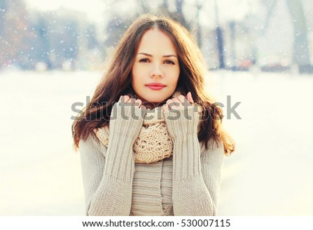 Portrait pretty young woman wearing a knitted sweater and scarf in winter day over snowflakes #530007115