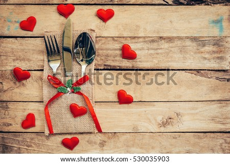 Table set for celebration Valentine's Day. Wooden table place setting and silverware with red heart for Valentine day. #530035903