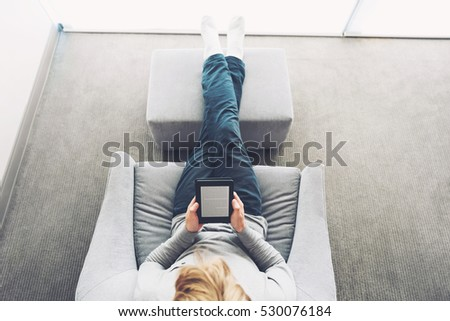 High view of a young blond man reading a book on digital device #530076184