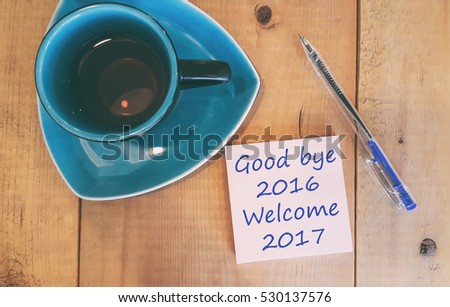 good bye 2016 Welcome 2017 - handwriting on paper with cup of tea and pen. #530137576