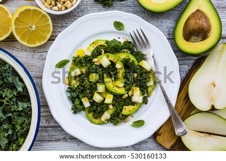 Fresh salad with kale leaves and avocado with pear on a white plate on wooden table.  #530160133