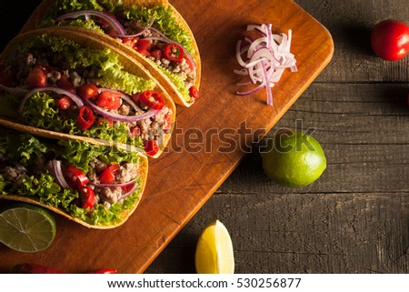 Photo of Mexican tacos with ground beef, onion, tomatoes, chili, red sauce, lettuce and lime on wooden background. Spicy and fast food concept.   #530256877