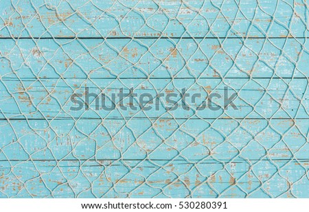Maritime nautical fishing net texture on turquoise blue wood background, copy space.  Royalty-Free Stock Photo #530280391