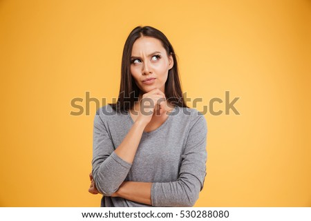 Thoughtful model in studio looking away. hand near the face. isolated orang background Royalty-Free Stock Photo #530288080