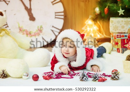 Little boy in a Christmas tree with gifts in his hands. Christmas. Gifts. The festive mood. Childhood . Joy