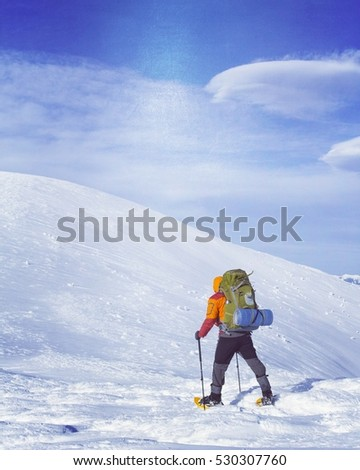 Winter hiking in the mountains on snowshoes with a backpack and tent. #530307760