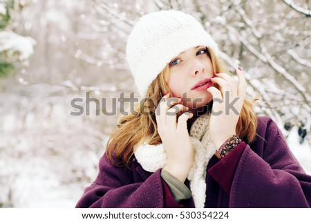 Beautiful young blonde woman in white wool hat and scarf. Portrait of beauty girl in knitted woolen winter clothing . #530354224