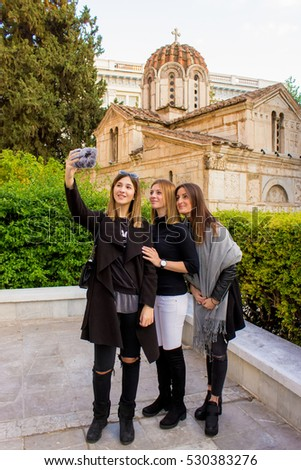 Three Caucasian women taking a selfie picture with mobile phone in front of a Greek Orthodox Christian church