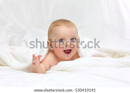 Baby in white bedding.