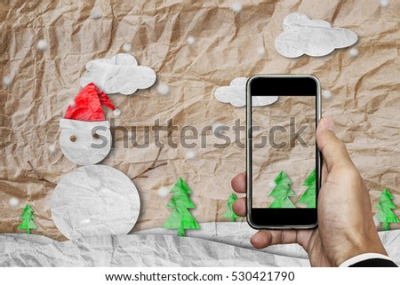 Smartphone on hand with blank screen, crumpled paper cut snowman in winter, with copy space on screen