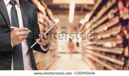 Businessman using the tablet and writing the order stock on Supermarket blur background, business technology concept Royalty-Free Stock Photo #530490646